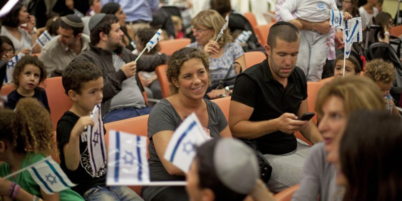 TEL AVIV, ISRAEL - JULY 16: (ISRAEL OUT) An estimated 400 new French Jewish immigrants wave Israeli flags during a welcoming ceremony after arriving on a flight from France on July 16, 2014 at Ben Gurion airport near Tel Aviv, Israel. Today Israel reportedly issued a warning to 100,000 residents of northern Gaza to evacuate their homes as it continues with planned airstrikes as part of operation 'Protective Edge'.  Israeli Prime Minister Benjamin Netanyahu said he had 'no choice' but to expand and intensify the military operation in light of the refusal to ceasefire terms from Hamas officials.  (Photo by Lior Mizrahi/Getty Images)