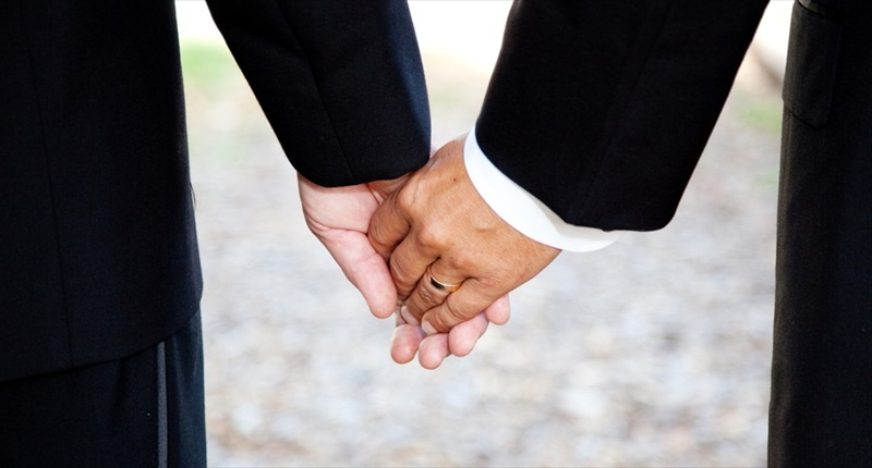 A-Gay-Couple-Holding-Hands-Wearing-A-Wedding-Ring-Shutterstock-800x430